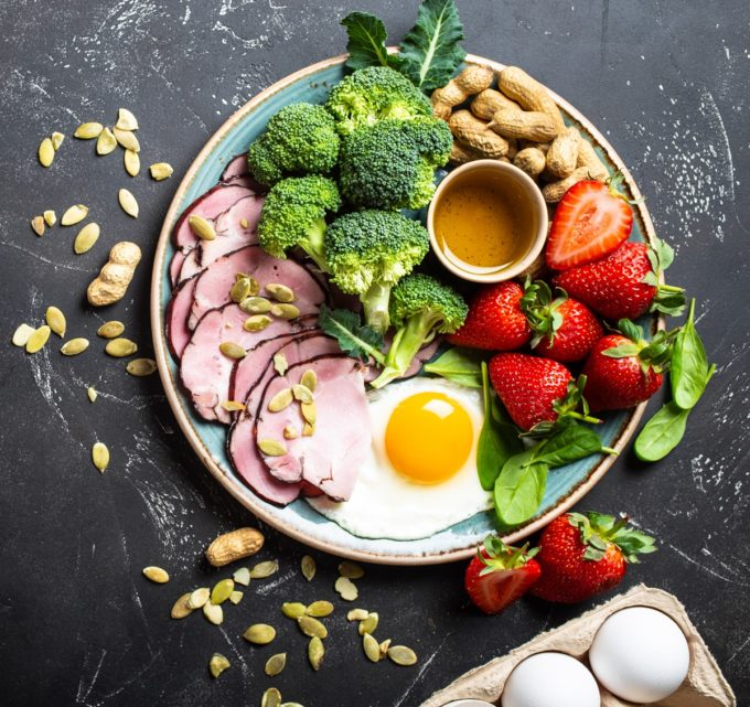 Ketogenic low carbs diet, top view, space for text. Plate on stone black background with keto foods: egg, meat, olive oil, broccoli, berries, nuts, seeds. Healthy fats, clean eating for weight loss